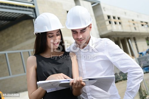 681142982 istock photo foreman architect man woman supervising building construction site with blueprint 484845358
