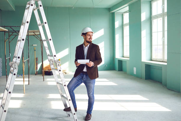 Foreman bearded man in a white helmet in a room at a construction site stock photo
