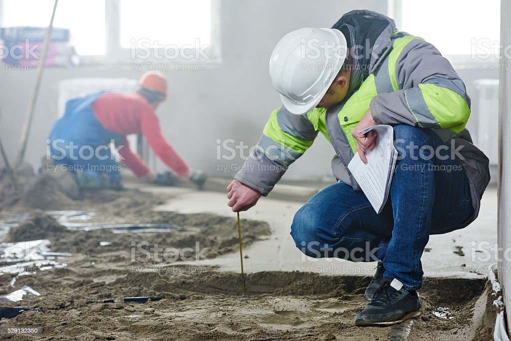 foreman builder inspecting concrete construction work in apartment stock photo