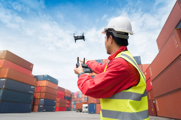 Foreman control drone to fly to survey the area worth in container yard stock photo