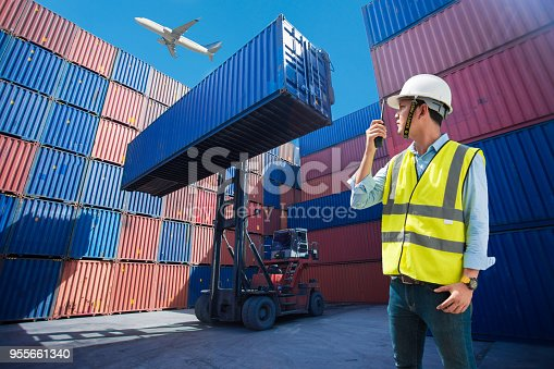 istock Foreman control loading Containers box from Cargo freight ship for import export, foreman control Industrial Container Cargo freight ship 955661340