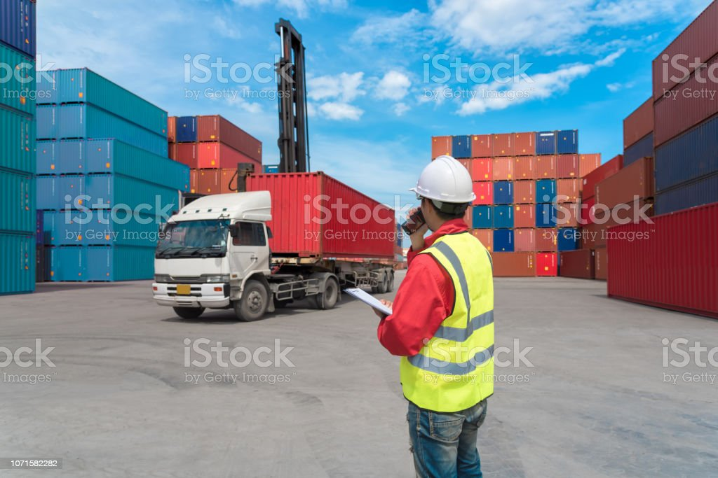 Foreman control loading Containers box from Cargo freight ship in...