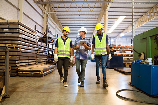 Foreman Discussing With Trainees In Factory Stock Photo - Download Image Now