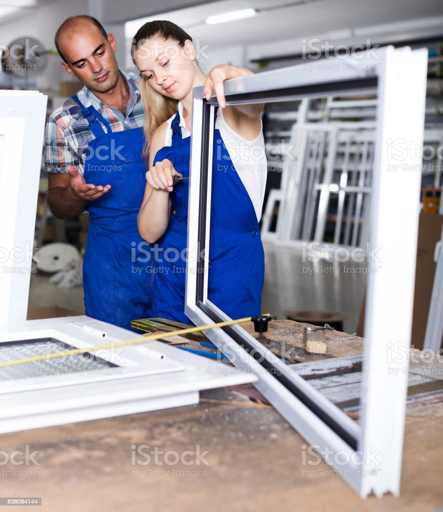 Foreman explaining plastic windows assembly process to young female worker stock photo