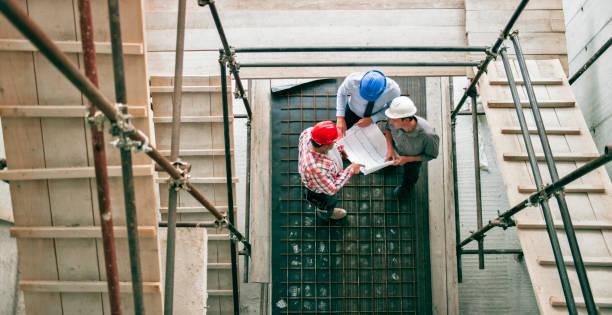 vorarbeiter geben fortschritt aktualisieren, investor und architekt stand sie am gerüst treppenhaus - projektmanager stock-fotos und bilder