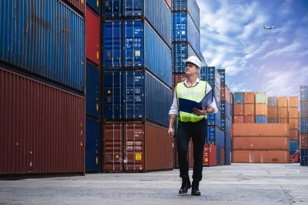 capataz segurando documento, caminhando e verificando a caixa de contêineres do cargueiro para exportação e importação - recipiente - fotografias e filmes do acervo