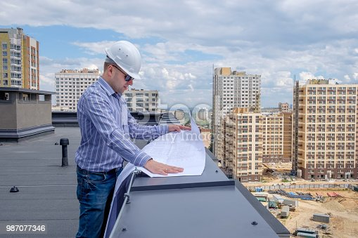 istock Foreman in white helmet and sunglasses on roof 987077346