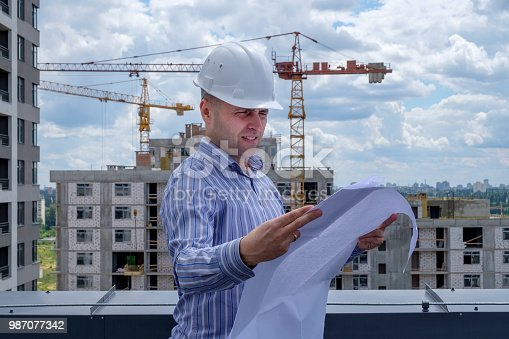 istock Foreman in white helmet on roof are looking at the project on the construction site. 987077342