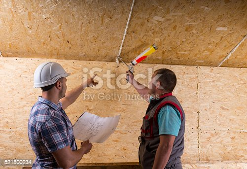 istock Foreman Instructing Worker How to Apply Caulk 521800234