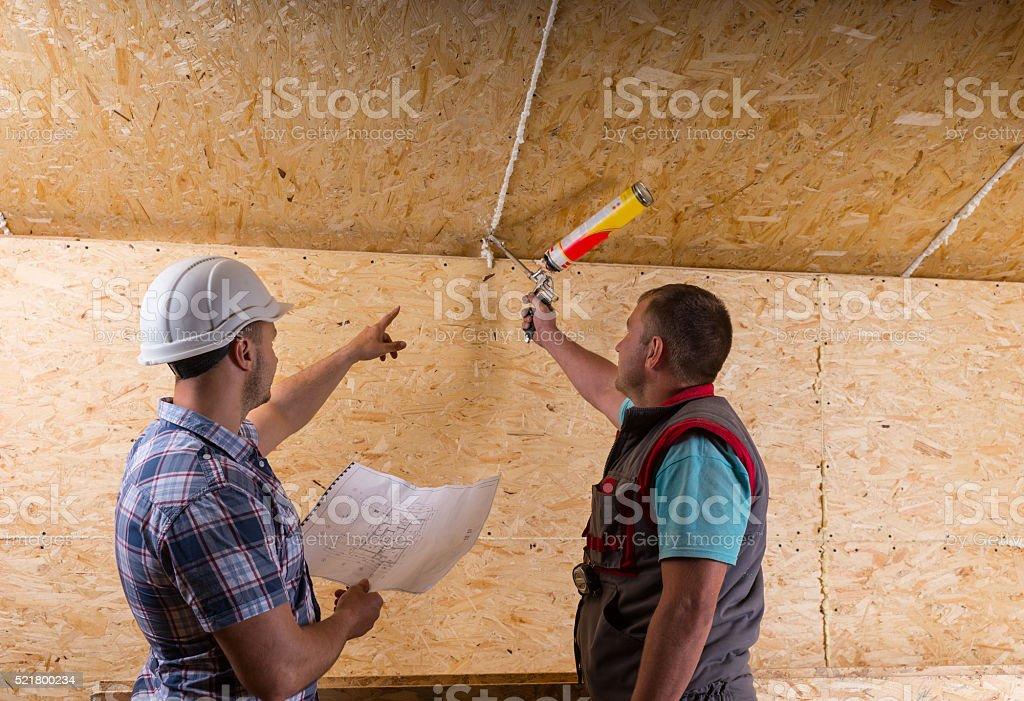 Foreman Instructing Worker How to Apply Caulk stock photo