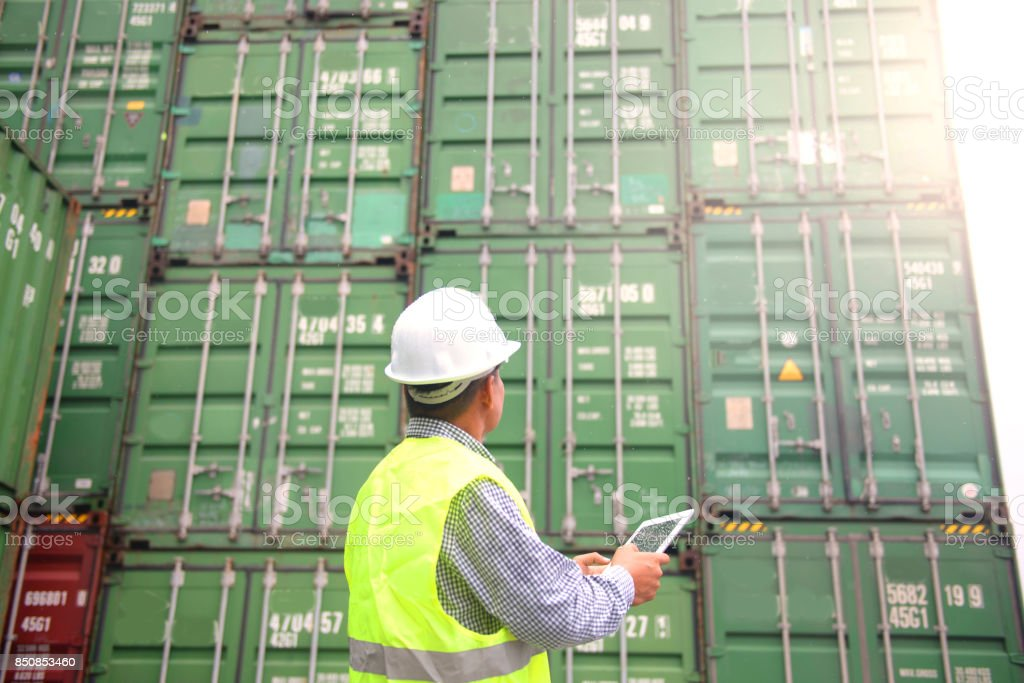 Foreman is using tablet to monitor inventory while working in the container depot. Foreman is using tablet to monitor inventory while working in the container depot. Adult Stock Photo