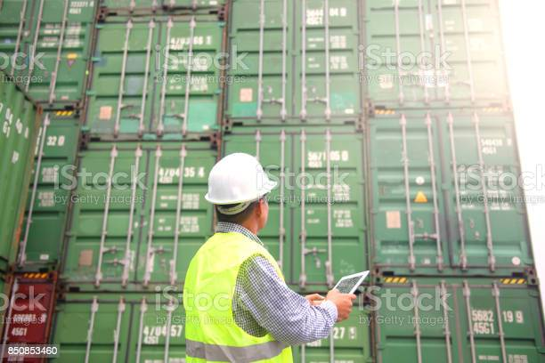 Foreman Is Using Tablet To Monitor Inventory While Working In The Container Depot Stock Photo - Download Image Now