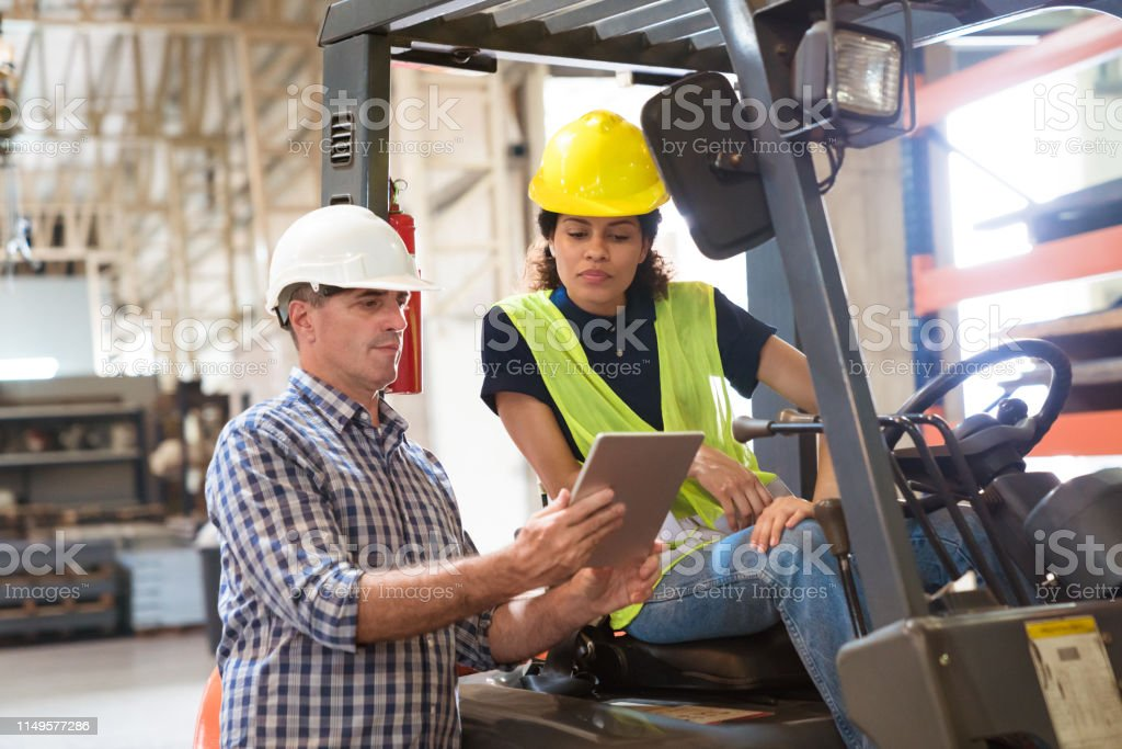 Foreman showing digital tablet to female colleague Mature foreman showing digital tablet to female colleague in factory. Confident worker is sitting on forklift. They are working together in distribution warehouse. 30-34 Years Stock Photo