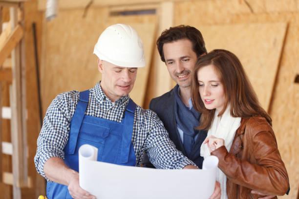 Vorarbeiter zeigt Hausentwurfspläne – Foto