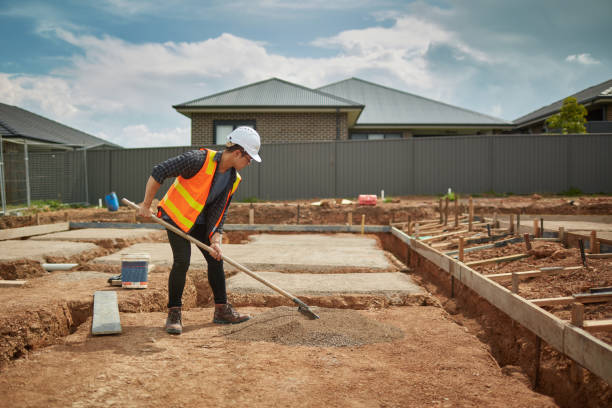 Foreman spreading dry cement at construction site stock photo