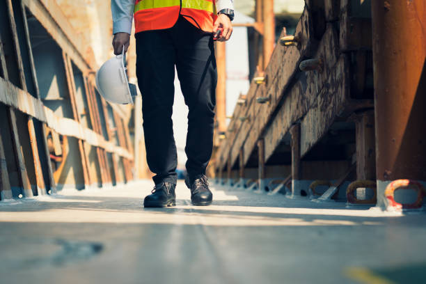 Foreman using walkie-talkie and safety boots to work in Cargo ship stock photo