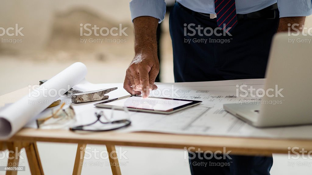 Foreman watching plans of storage rooms on digital tablet stock photo