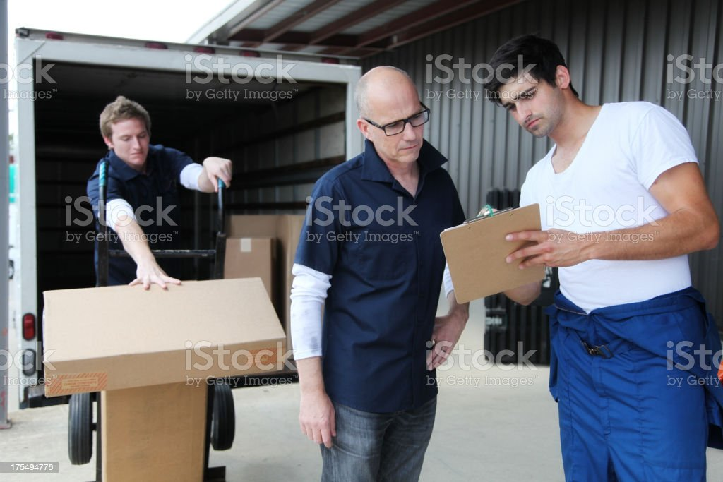 Foreman with Clipboard, and Workers Loading Moving Truck royalty-free stock photo