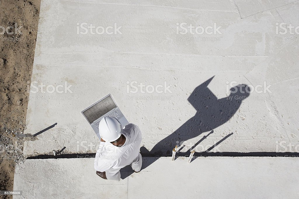 Foreman with laptop at new construction site stock photo