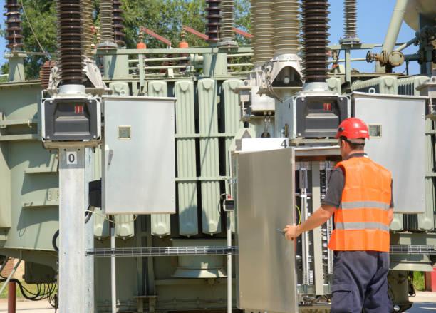 Vorarbeiter im Kraftwerk in der Nähe von Transformatoren arbeiten. – Foto