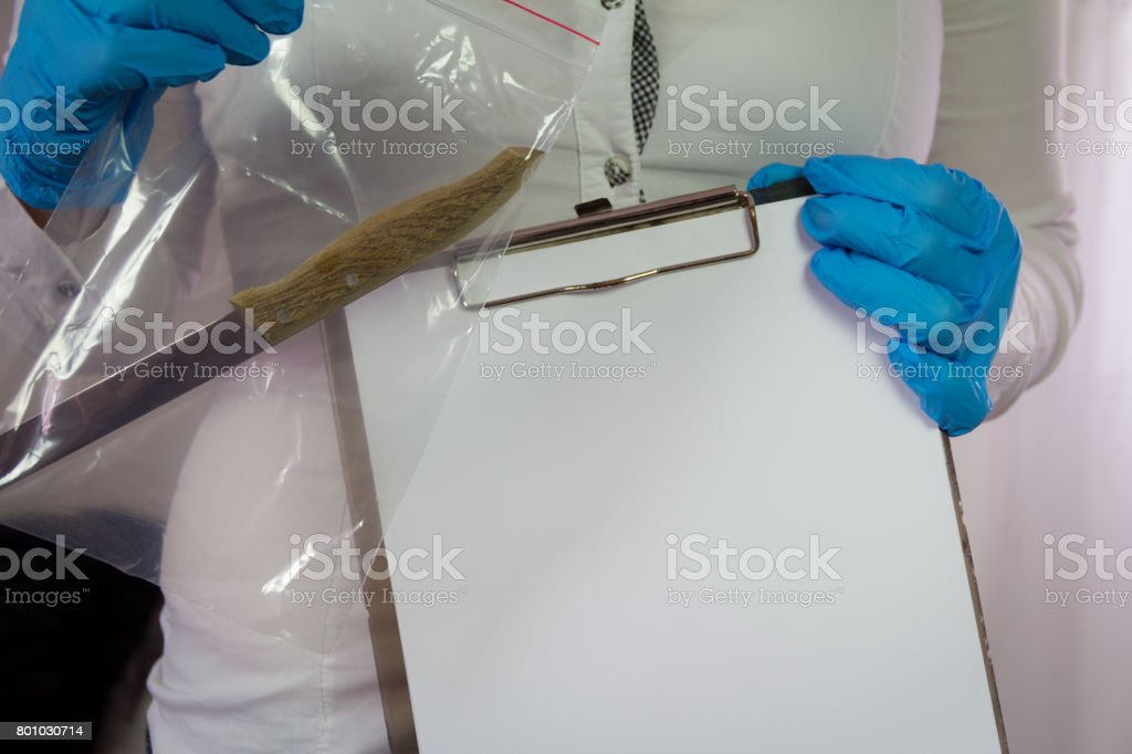 A forensic expert analyzes the knife that killed him stock photo