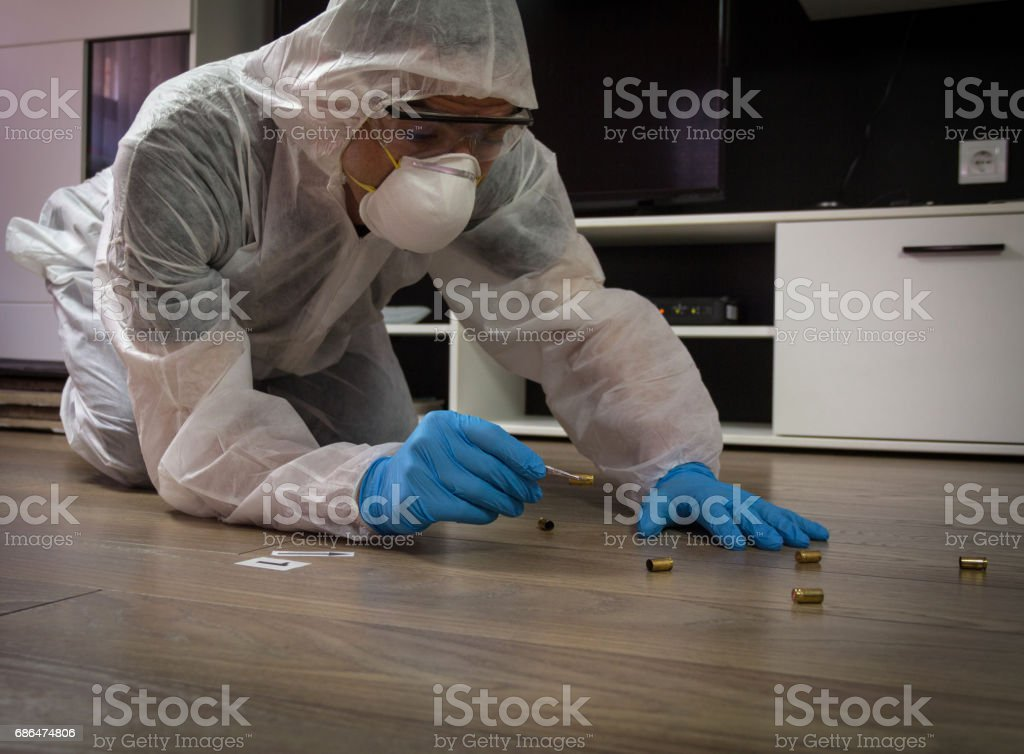 Forensic expert collecting bullet casings found at the crime scene stock photo