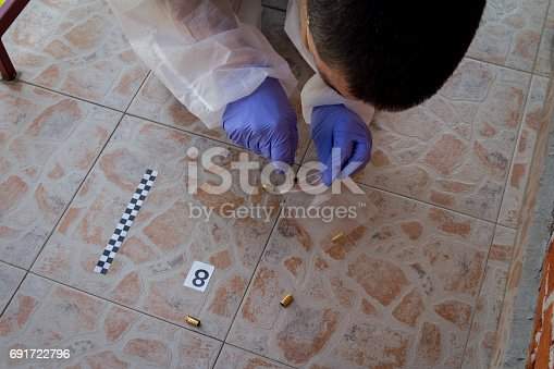 istock Forensic expert collecting shell casings in the bag found at the crime scene 691722796
