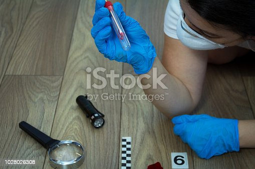 istock A forensic expert takes a blood sample with a sterile stick 1028026308
