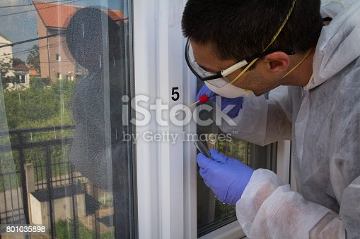 istock Forensic expert takes a sample of the DNA analysis on sterile swab from the window 801035898