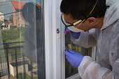 Forensic expert takes a sample of the DNA analysis on sterile swab from the window