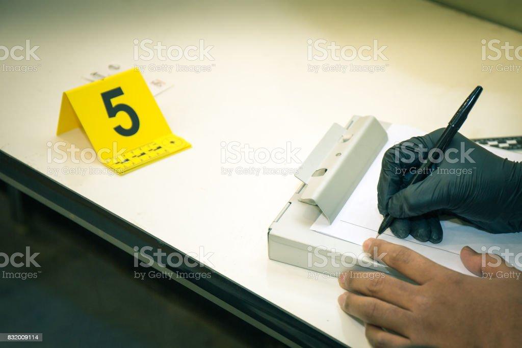 forensische Hände im Handschuh Beweise Informationen mit Beweise Marker schreiben – Foto