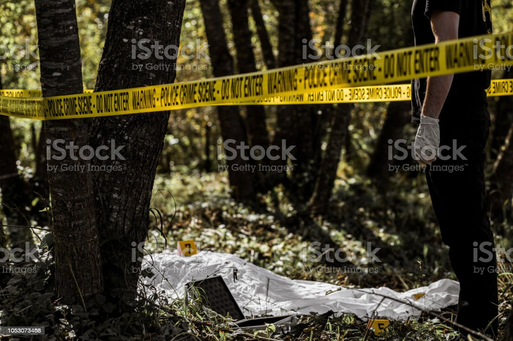 Forensic Looking At Dead Body On The Ground Stock Photo