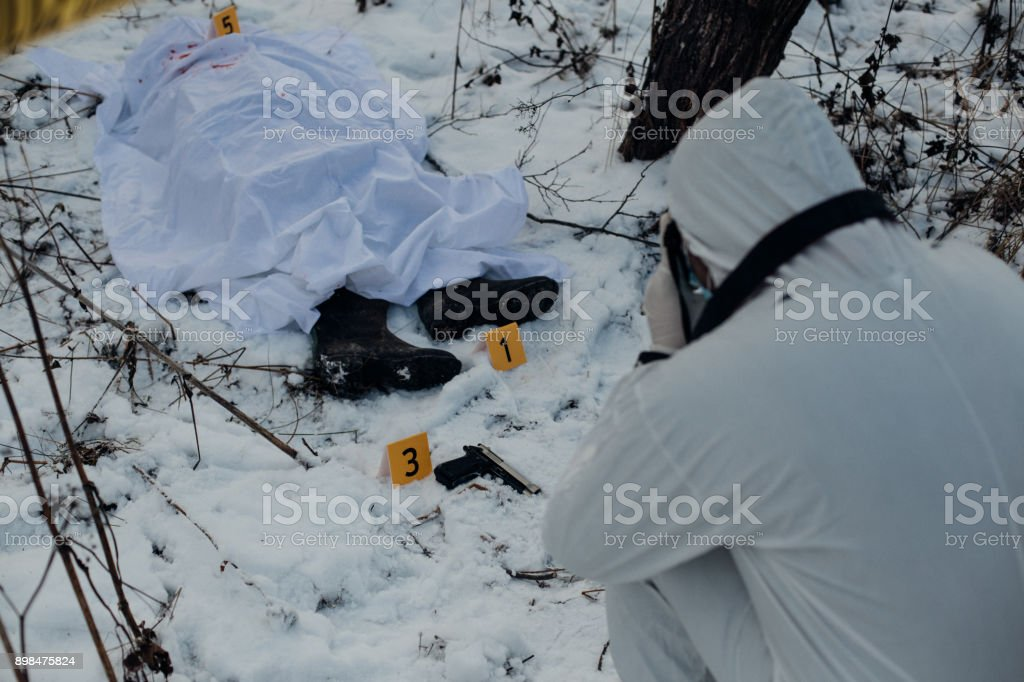 Forensic photographing evidence in the snow in a crime scene investigation stock photo