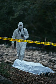 A forensic scientist is seen holding a camera and going towards the dead body that is lying on the ground near rocks. The cordon tape is in the middle of a picture.