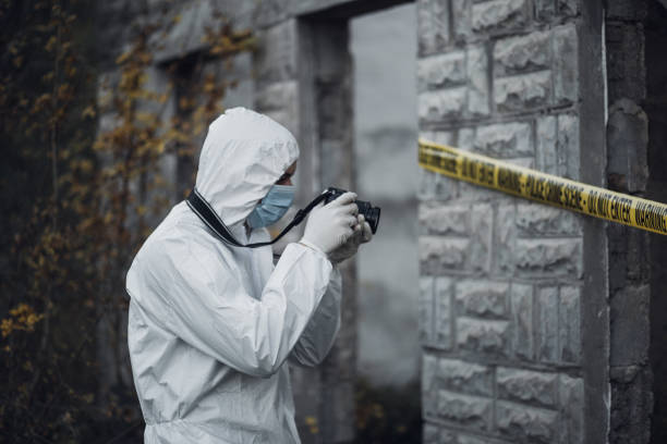 Forensic scientist photographing a building in a crime scene stock photo