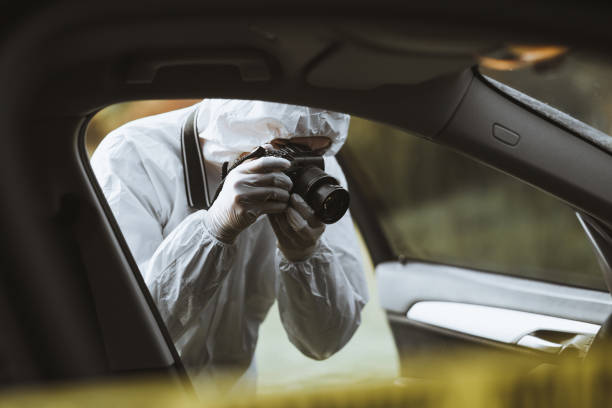 Forensic scientist photographing a car interior stock photo