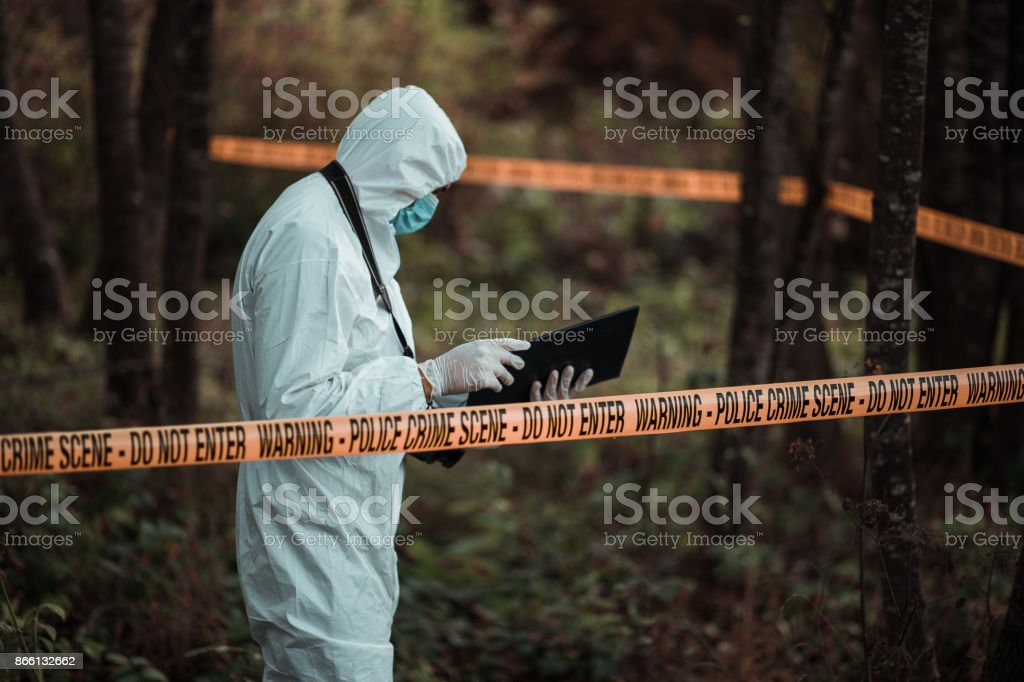 Forensic scientist reading notes in a crime scene area stock photo