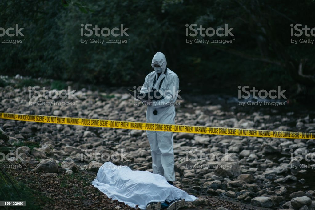 Forensic scientist taking a note near the dead body in the woods stock photo