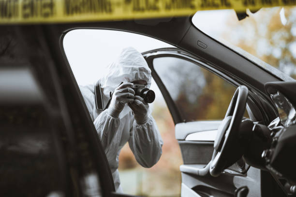 Forensic scientist taking a picture of a car interior stock photo