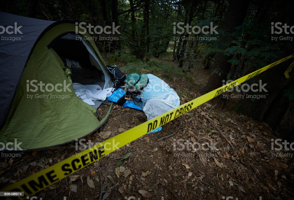 Forensics researcher photographing a blood  at a murder scene stock photo