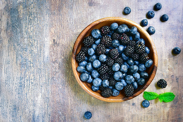 Forest berries (blueberry,bramble) in a wooden bowl.Top view. – Foto