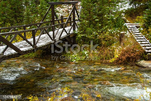 forest bridge over river with wooden railings under first snow, danger ice on bridge