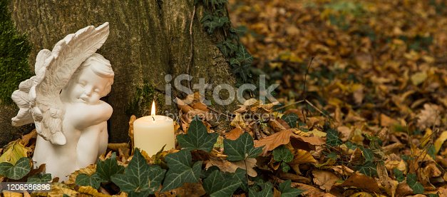 Forest cemetery, angel with candles on tree trunk, nature funeral