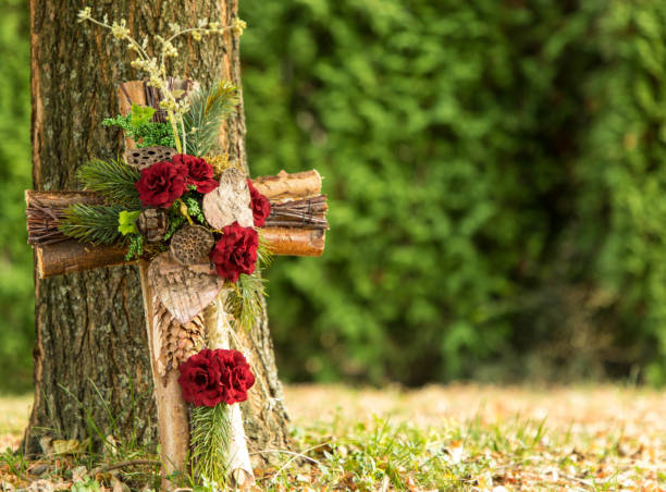 Forest burial, cross on tree trunk stock photo