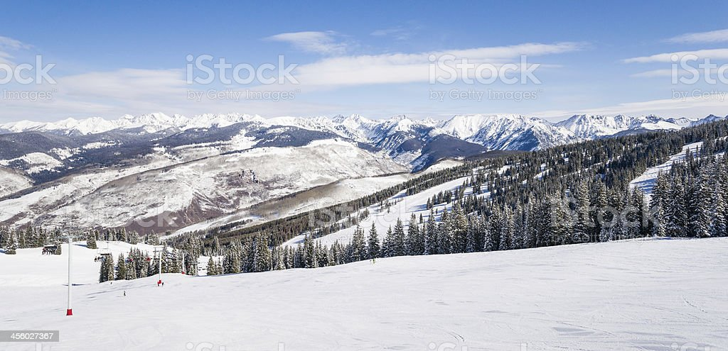 Forest Covered by Snow with Skiing Slopes and Rocky Mountains royalty-free stock photo