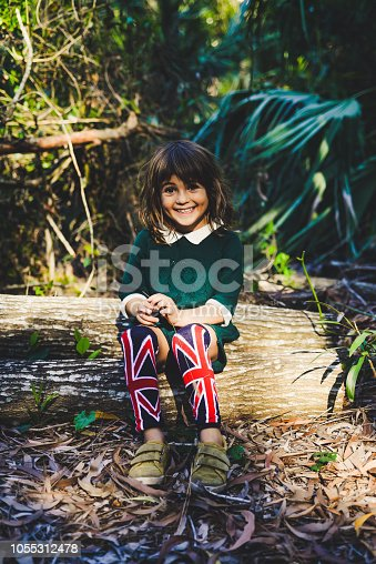 Little girl, 4 years old, in a green collared jumpsuit  in a wooded forest setting. She has on sneakers and cute British flag knee socks. Outdoors, childhood, and a cute kid. Smiling, happy, candid. She is smiling and sitting on a log