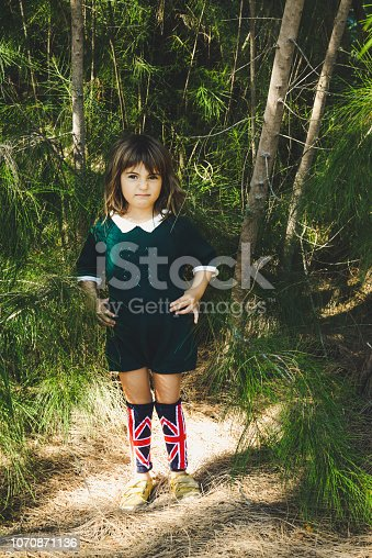 Little girl, 4 years old, in a green collared jumpsuit  in a wooded forest setting. She has on sneakers and cute British flag knee socks. Outdoors, childhood, and a cute kid making a funny face with a scrunched up nose, she looks displeased