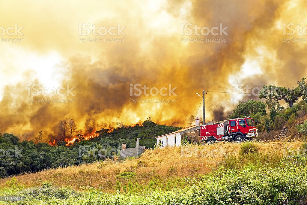 Forest fire near a rural home and fire truck in Portugal stock photo