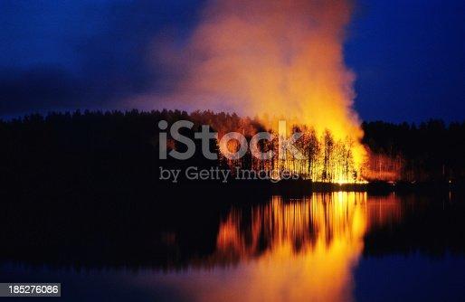Night scene of forest fire with trees in silhouette and relection in lake. Scanned from film.