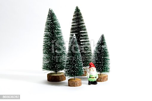 Isolated group of full artificial firs like a small forest tree with a figurine of garden gnome inside on a white background. Minimal still life photography